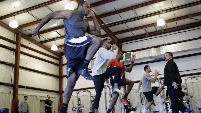 In this Feb. 14, 2014 photo, coach Geir Gudmundsen, right, looks on as players work on running techniques at TEST Sports Clubs in Martinsville, N.J. More than 300 NFL hopefuls will be measured on their 40-yard dash times, 225-pound bench press reps and other tests at the scouting combine in Indianapolis this week. Many college players get crash courses in everything from improving their performance in the physical tests to preparing for the intelligence at training centers like TEST Sports Clubs. (AP Photo/Mel Evans)
